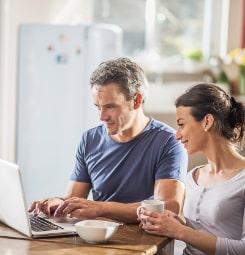 Dwoje ludzi siedzących przed laptopem